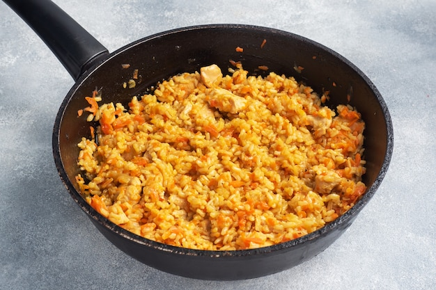Вкусный азиатский плов, тушеный рис с овощами и курица на сковороде. серый бетонный фон. копировать пространство.