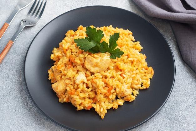 おいしいアジアのピラフ、野菜と鶏肉の煮込みご飯。灰色のコンクリートの背景。