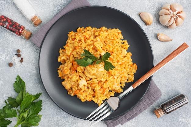 Вкусный азиатский плов, тушеный рис с овощами и курицей на тарелке. серый бетонный фон.