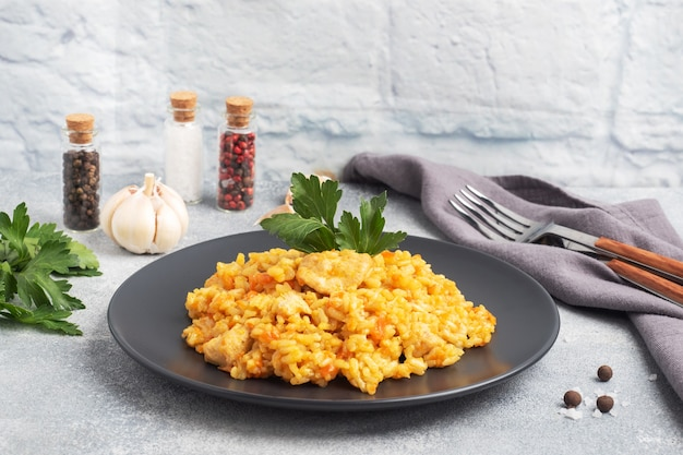 Delicious asian pilaf, stewed rice with vegetables and chicken on a plate. gray concrete background. copy space.