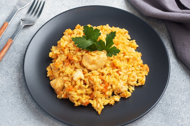 Delicious asian pilaf, stewed rice with vegetables and chicken on a plate. gray concrete background.