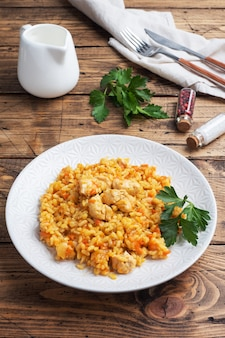 Delicious asian pilaf, stewed rice with vegetables and chicken on a plate. wooden rustic background.