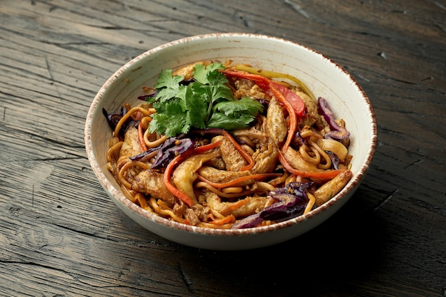 맛있는 아시아 거리 음식-나무 표면에 흰색 그릇에 닭고기, 실란트로, 야채와 스크램블 에그와 계란 국수