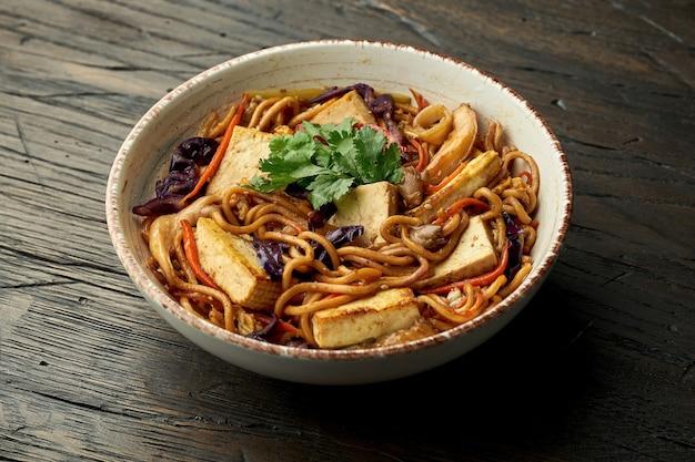 맛있는 아시아 거리 음식-나무 표면에 흰색 그릇에 두부, 고수, 야채와 스크램블 에그와 계란 국수