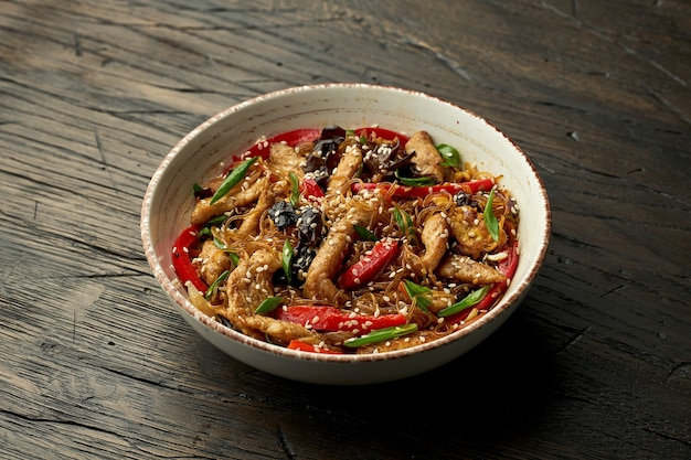 Delicious asian street food - funchose noodles with chicken, cilantro, vegetables and omelet in a white bowl on a wooden surface