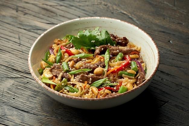 おいしいアジアの屋台の食べ物-木の表面の白いボウルに牛肉、コリアンダー、野菜、スクランブルエッグを詰めたタイの麺