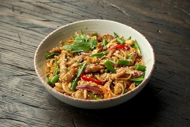 おいしいアジアの屋台の食べ物-木の表面の白いボウルにチキン、コリアンダー、野菜、スクランブルエッグを詰めたタイの麺