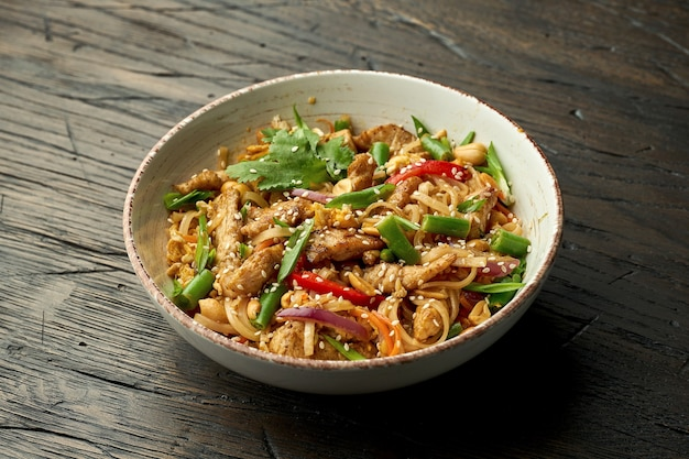 Delicious asian street food - pad thai noodles with chicken, cilantro, vegetables and scrambled eggs in a white bowl on a wooden surface