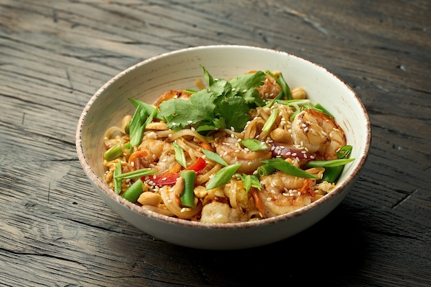 おいしいアジアの屋台の食べ物-木の表面の白いボウルにエビ、コリアンダー、野菜、スクランブルエッグを詰めたタイの麺