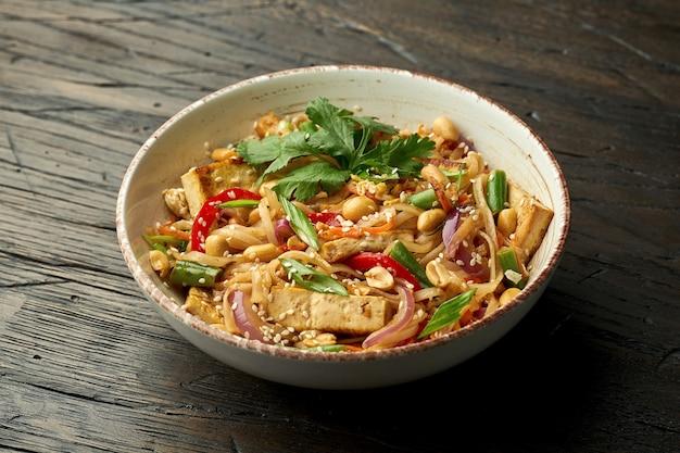 おいしいアジアの屋台の食べ物-木の表面の白いボウルに豆腐、コリアンダー、野菜、スクランブルエッグを詰めたタイの麺