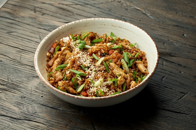 Delicious asian street food - wok rice with chicken, green onions, vegetables and sesame seeds in a white bowl on a wooden surface