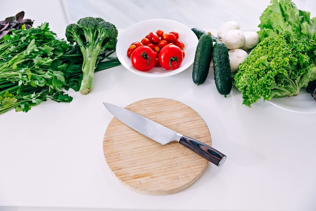 Delicious assortment of farm fresh vegetables with knife on white wooden background top view