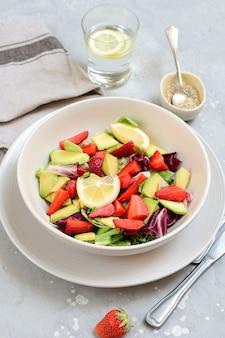 白い皿にイチゴのおいしいアボカドサラダ。ケト料理レシピ。ヘルシーランチ