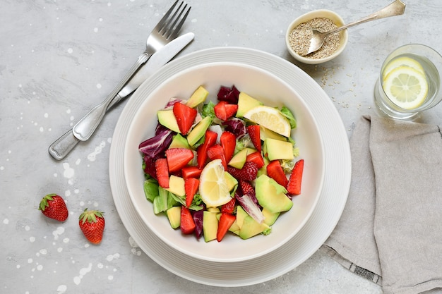 Delicious avocado salad with  strawberries on a white plate. keto food recipe. healthy lunch