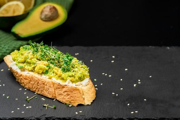 Вкусный тост из авокадо с оливковым маслом, помидорами и микрозеленью и семенами кунжута на тосте из багета со сливочным сыром. крупный план с копией пространства, половина авокадо рядом на черном столе Premium Фотографии