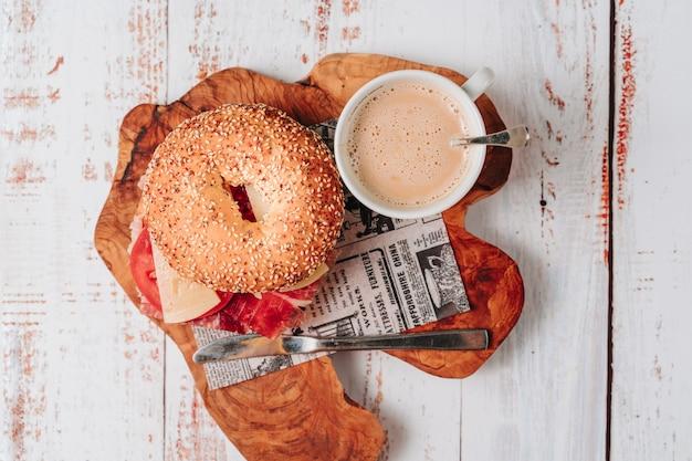 ゴマとチアのパンが入ったおいしいベーグルには、トマト、ハム、フレッシュチーズ、抽出したてのアボカドのスライスが入っています。