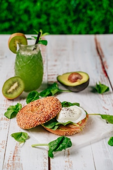 Delicious bagel with sesame and chia bread, inside it contains salmon, fried egg and basil.