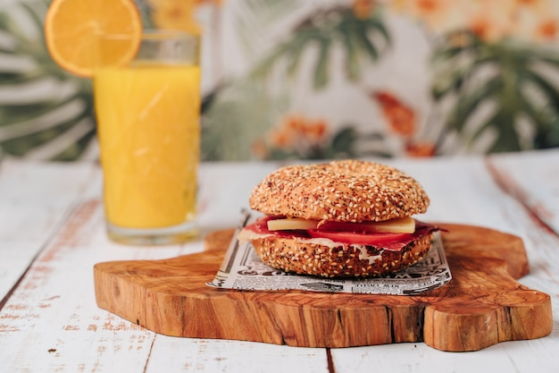 Delicious bagel with sesame and chia bread, inside it contains tomato, ham and chicken in strips.