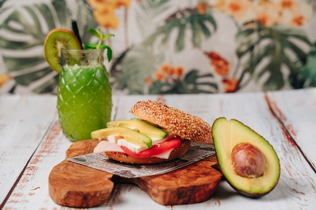 Delicious bagel with sesame and chia bread, inside it contains tomato, ham, fresh cheese and some freshly extracted slices of avocado.