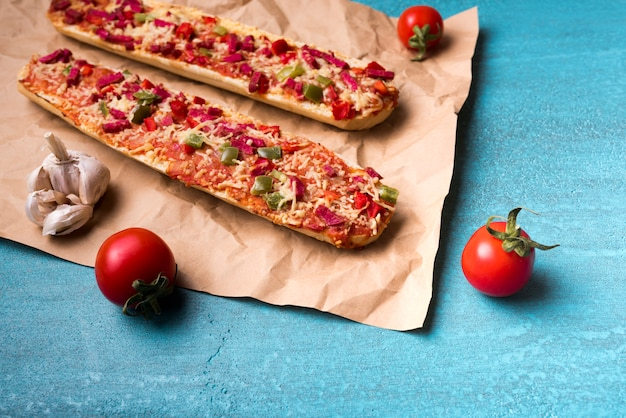 Delicious baguette pizza; cherry tomato and garlic on brown paper over blue concrete backdrop