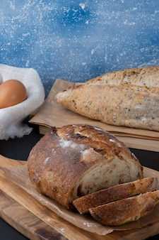 Delicious baked breads on cutting board.