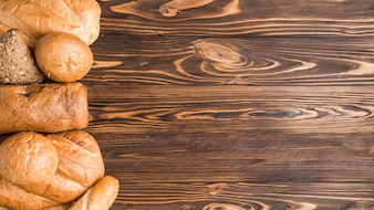 Delicious baked breads on wooden backdrop