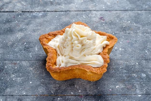 Deliziosa torta al forno a forma di stella con crema bianca gustosa all'interno sulla scrivania luminosa, tè alla crema dolce e zucchero da forno