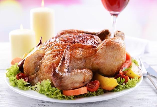 밝은 배경에 있는 테이블에 있는 맛있는 구운 치킨