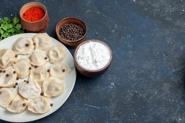 Вкусные запеченные пельмени внутри тарелки вместе с перцовым йогуртом и зеленью на сером столе, обед из теста, калорийность мяса