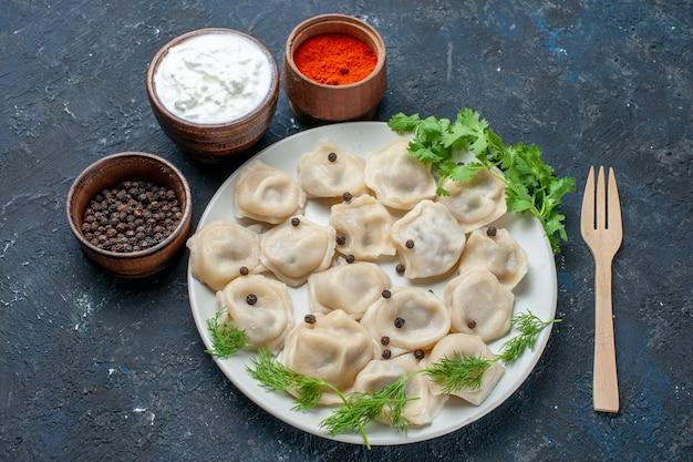 Вкусные запеченные пельмени внутри тарелки вместе с йогуртом и зеленью на темно-сером столе, обед мясная калорийная еда
