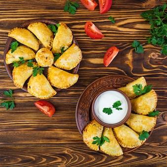 Delicious baked empanadas on wooden background