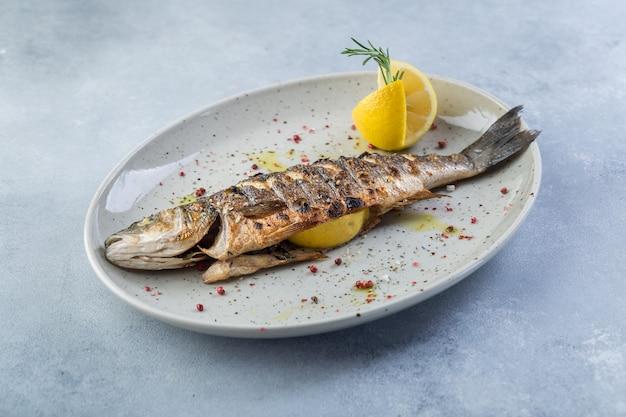 Вкусная запеченная рыба с лимоном и специями на белой тарелке. оригинальная презентация. центральная