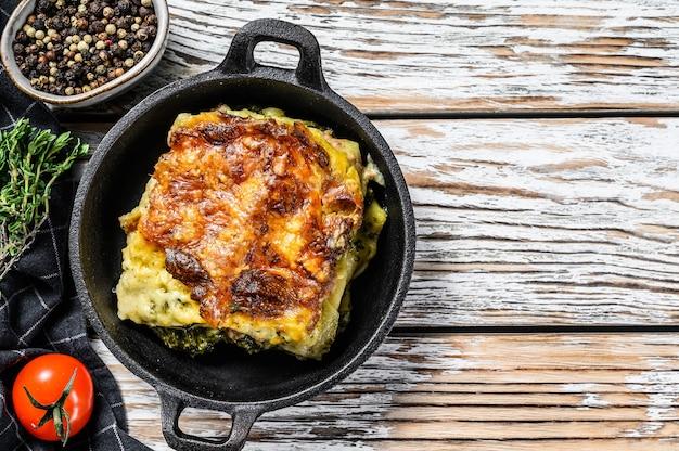 鍋に焼き上げたおいしいラザニア、イタリアの伝統料理。白い木の背景。上面図。スペースをコピーします。