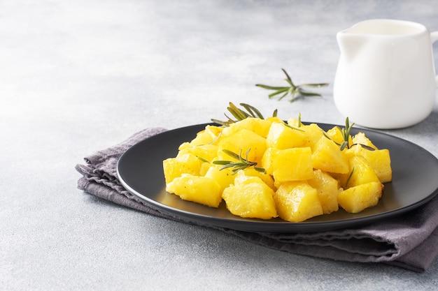 黒いセラミックプレート、灰色のコンクリートの背景、コピースペースにスパイスチーズとローズマリーを添えたおいしいベイクドポテト。