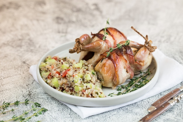 Delicious baked quail with bacon and side dish