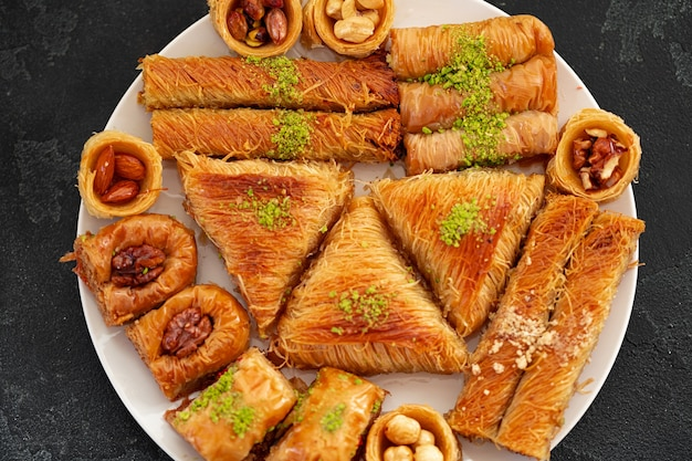 Delicious baklava dessert in oriental setting on black background