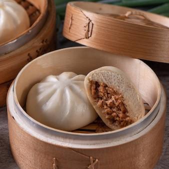 おいしい包子、中国の蒸し肉パンは、サービングプレートと蒸し器ですぐに食べられます。クローズアップ、コピースペースの製品デザインコンセプト。