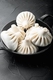 Вкусные баоцзы, китайские мясные булочки на пару в сковороде на черном каменном фоне