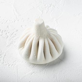 Вкусные баоцзы, китайские мясные булочки на пару, в пластиковом подносе, на белой каменной поверхности, квадратный формат