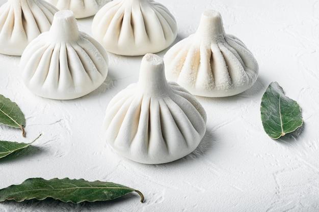 Вкусные баоцзы, китайские мясные булочки, приготовленные на пару, на белой каменной поверхности