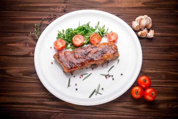 Delicious barbecued ribs seasoned with a spices and fresh herbs on wooden background