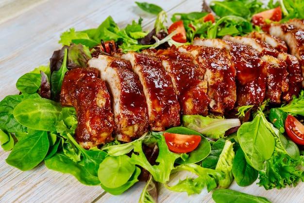 Вкусные свиные ребрышки барбекю с зеленым салатом и острым соусом барбекю.