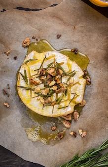 꿀, 호두, 허브 및 배와 함께 맛있고 아름다운 구운 카망베르
