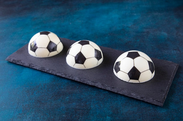 Delicious beautiful dessert in the shape of three halves of the ball - sweet cakes on a black serving board. creative designer pastries for snacks while watching football matches