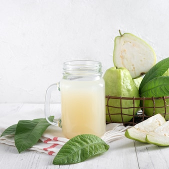 Delicious beautiful guava fruit with fresh juice set isolated on bright white wooden table background, close up.