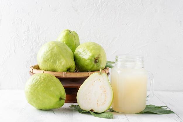 明るい白い木製のテーブルの背景に分離されたフレッシュジュースセットとおいしい美しいグアバフルーツ、クローズアップ。