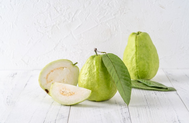 Delicious beautiful guava set with fresh leaves isolated on bright white wooden table background, close up.