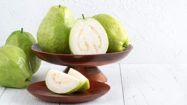 明るい白い木製のテーブルの背景に分離された新鮮な葉で設定されたおいしい美しいグアバ、クローズアップ。