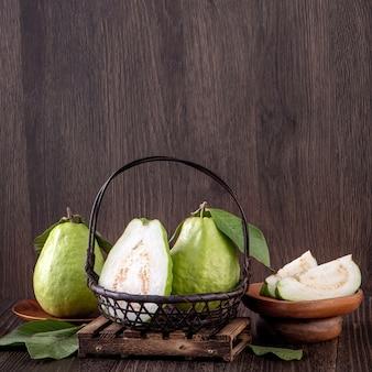 木製のテーブルの背景に分離された新鮮な葉で設定されたおいしい美しいグアバ、クローズアップ。
