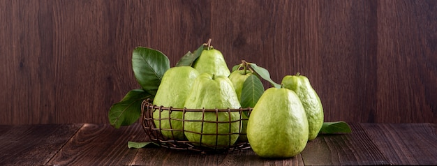 Delicious beautiful guava set with fresh leaves isolated on wooden table background, close up.
